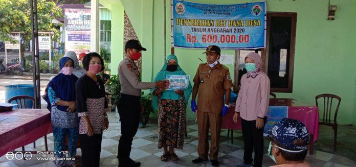 Kepala Desa, Erwin Sibagaring bersama pihak kepolisian saat menyerahkan bantuan langsung tunai kepada masyarakat. Foto: istimewa